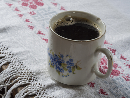 old chipped cup with painted forget-me-not with black coffee on rustic embroider tablecloth