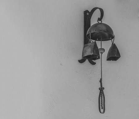 rusty background: old rustic warning bell cow bell hanging from the white wall in black and white Stock Photo