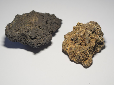 close up ochre and beige gray natural lava stones on white background Stock Photo