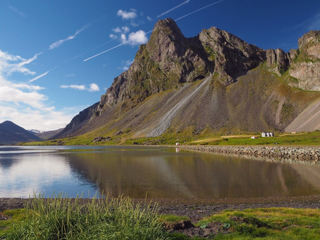 view on mountains green grass and sea lake on eastern fjords Iceland