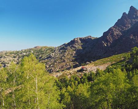 France, Corse, Haut Corse, June 13, 2017: View on refuge Ortu di Piobbu first part of GR 20 famous trek with green birche tree sharp mountain peak and blue sky