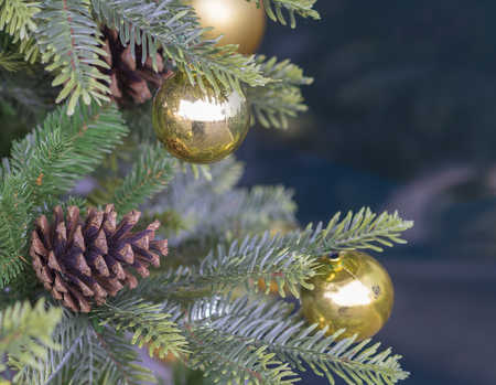 close up pine tree cone and golden christmas balls on artificial christmas tree with blue bokeh background Stock Photo