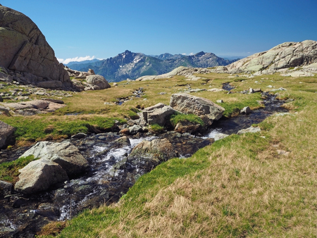 summer scenery of high snow covered mountain corsician alpes with beatiful mountain stream spring on green meadow and rocks boulders with blue sky background Stock Photo