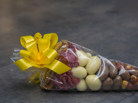 close up gift cellophane cone full of luxury dried fruit chocholate nuts with yelow topknot on grey decorative background