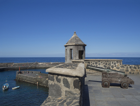 old copper cannon on paved sea front with embrasure tower, stone wall, sea horizon, fisherman boat and bathing people with clear blue sky background in Peurto de la Cruz, Tenerife