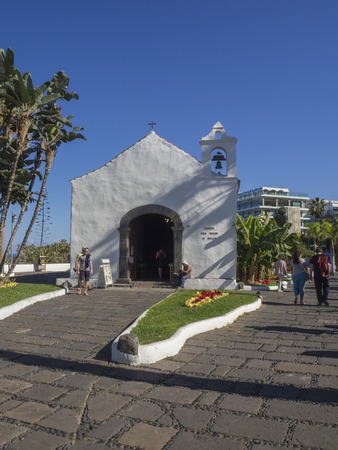 Spain, Canary islands, Tenerife, Puerto de la cruz, December 23, 2017, old small white church and group of walking tourist on promenade, blue sky background Editorial