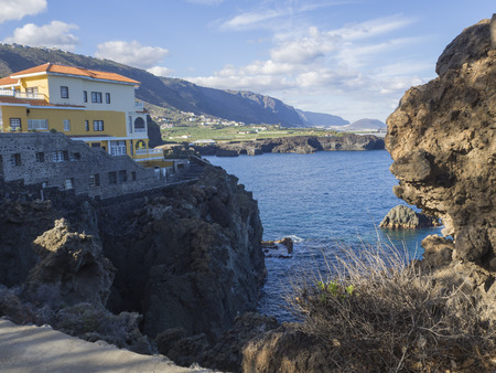 View on bay in San Marcos village with sharp rock and cliffs and villa on Tenerife, sea and blue sky background