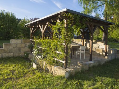 brown tiber wooden gazebo or pergola with climbing plants and flowers,  table and chairs and - Brown Tiber Wooden Gazebo Or Pergola With Climbing Plants And