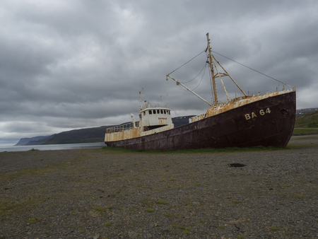 Iceland, west fjords, Patreksfjordur, June 24, 2018: Old abandoned rusty fishing boat ship wreck standing on the sand beach coast in west fjords od Iceland, dramatic gray sky and cliffs background Redakční