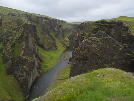 View on river stream and green moss covered cliffs and hills in Eldgja gorge in Iceland, grass with flowers and blue sky background Banque d'images