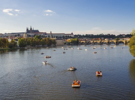 panorama of Charles bridge over Vltava river and Gradchany, Prague Castle and St. Vitus Cathedral. Czech Republic, golden hour light, summer sunny day, tourists relaxing on boats 版權商用圖片