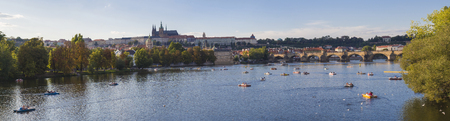 Wide panorama of Charles bridge over Vltava river and Gradchany, Prague Castle and St. Vitus Cathedral. Czech Republic, panoramic view, golden hour light, summer sunny day, tourists relaxing on boats 版權商用圖片