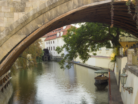 Czech Republic, Prague, September 8, 2018: Certovka river, Devils Channel, also called Little Prague Venice between Kampa island and Mala strana in Czech Republic with Historic Mill Wheel and boat seen under Bridge arc