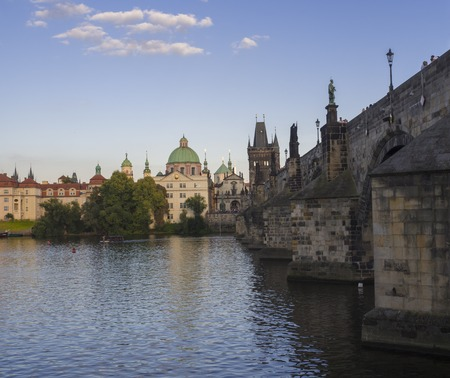 View of Charles Bridge in Prague from Kampa, Czech Republic. Gothic Charles Bridge is one of the most visited sights in Prague. Architecture and landmark of Prague, golden light, sunny summer day.