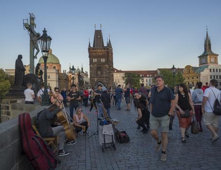 Czech Republic, Prague , September 8, 2018: View from Charles Bridge on Mala Strana Bridge Tower with walking tourist people, street artist and souvenir sellers at sunset