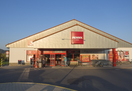 Czech republic, Cvikov, October 14, 2018: Entrance of Penny discount supermarket and shopping people, autumn sunny day, blue sky