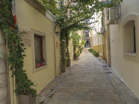 Greece, corfu, Kerkyra town, september 26, 2018: Corfu old town narrow cobblestone street with flower garlands in flower pots, summer day.