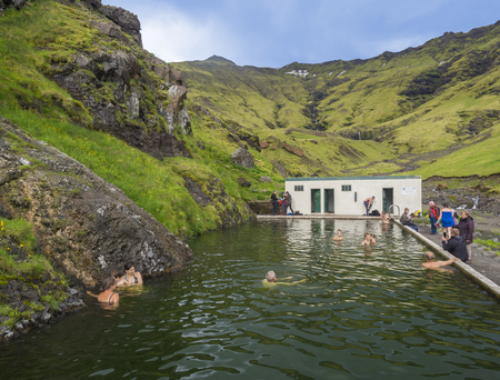 South Iceland, Seljavellir, July 4, 2018: People swimming and enjoying green warm water in Seljavallalaug secret geothermal pool hiden in valley with green hills