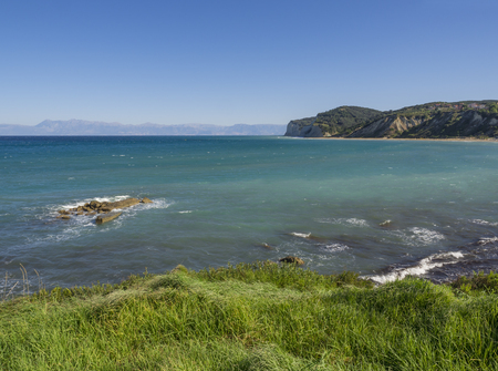View on agios stefanos beach and bay with lush green grass and steep cliffs, north east coast of Corfu in Greece, summer day blue sky Standard-Bild