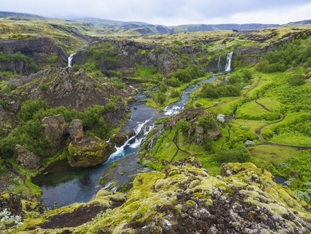 Beautiful Valley Gjain with colorful lava rocks, lush green moss and vegetation and blue water with waterfalls and cascade in south Iceland