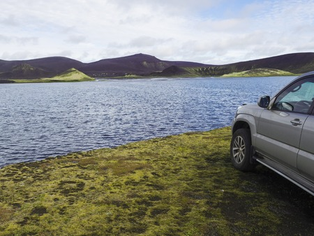 4x4 off road car standing on banks of blue crater lake and volcanic purple and green mountains in Veidivotn lakes, popular fishing area for local, central Iceland highlands in the middle of black lava desert 写真素材