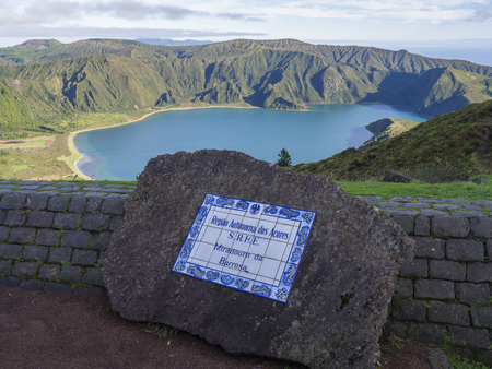 View on beautiful blue crater lake Lagoa do Fogo from viewpoint miradouro da barrosa. and sign on ceramic deskon stone. Lake of Fire is the highest lake of Sao Miguel island, surrounded by Natural Reserve green