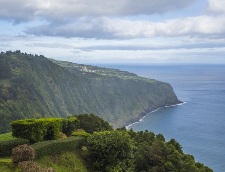 view with steep cliffs, sea, hedge bush and flower garden from the viewpoint Miradouro da Ponta do Sossego at Nordeste on Sao Miguel island, Azores, Portugal Фото со стока