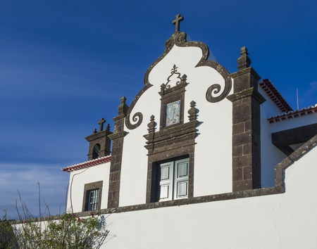 Detail of front facade of white Marian sanctuary of Nossa Senhora da Paz, Our Lady Of Peace Chapel, beautiful small chapel on a high hill above the village of Vila Franca do Campo in Sao Miguel island Azores, Portugal, blue sky background 版權商用圖片 - 117195968