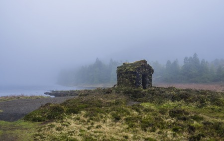 little stone hut covered by moss at the shallow banks of lake Lagoa Rasa surrounded by green forest lost in mist. mysterious moody day, the island of Sao Miguel, Azores, Portugal