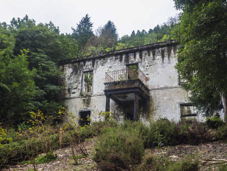 Abondoned ruin of historical villa house in tropical forest on footpath hiking trail near Furnas, Sao Miguel island, Azores, Portugal