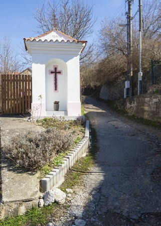 small white wayside shrine, road blessing or Gods torture with cross next village road curve in Srbsko, Czech republic Archivio Fotografico