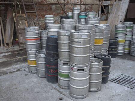 Beroun, Czech Republic, March 23, 2019: close up Pilled empty metal barrels or kegs of czech beer on yard along of brick wall outside of Beroun brewery called Berounsky medved. Editorial