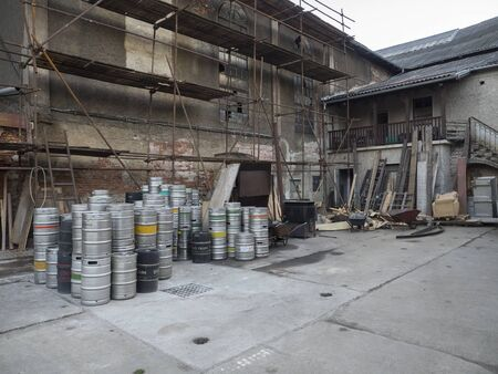 Beroun, Czech Republic, March 23, 2019: courtyard of Beroun brewery called Berounsky medved with pile of empty metal barrels or kegs of czech beer, copy space