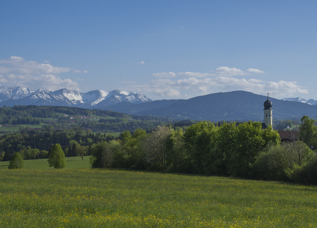 Beautiful spring rural mountain landscape in the Bavarian Alps with church village and snow covered mountain peaks massif in the background. Bavaria, Germany 写真素材