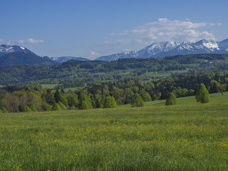 Beautiful spring rural mountain landscape in the Bavarian Alps with village and snow covered mountain peaks massif in the background. Bavaria, Germany