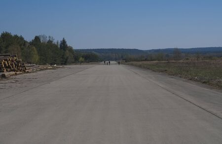 People using former soviet army military airport for having fun on in-line skates. Czech Republic, Ralsko. Springtime, blue sky.