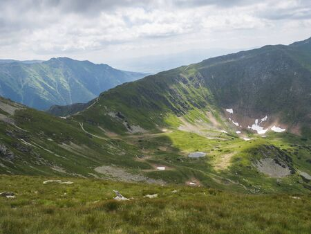 view from Ostry Rohac peak on Western Tatra mountains or Rohace panorama. Sharp green mountain peaks with hiking trail on ridge. Summer blue sky white clouds. Imagens