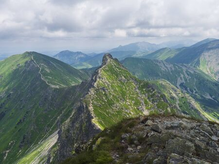 view from Ostry Rohac peak on Western Tatra mountains or Rohace panorama. Sharp green mountain peak placlive with hiking trail on ridge. Summer blue sky white clouds.