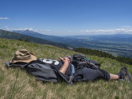 man hiker in hat taking a nap at meadow with Mountain landscape of Western Tatra mountains or Rohace with view on high tatras with Krivan peak from hiking trail on Baranec. Summer blue sky background Imagens