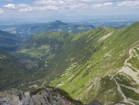 View from the Smutne sedlo saddle on Smutna dolina valley with Beautiful blue mountain lake Tatialkovo jezero with green mountain peaks , Western Tatras mountains, Rohace Slovakia, summer sunny day blue sky Imagens