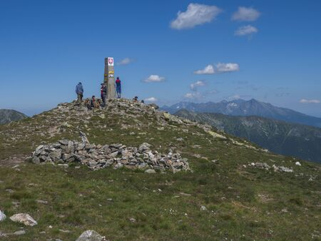 Slovakia, Western Tatra mountain, July 4, 2019: group of hiker people resting on top of Baranec peak in Western Tatra mountains with Rohace panorama. Sharp green mountains with hiking trail on ridge. Summer blue sky background