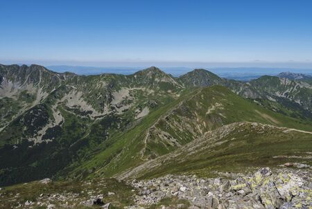 Beautiful mountain landscape of Western Tatra mountains or Rohace with hiking trail on ridge. Sharp green grassy rocky mountain peaks with scrub pine and alpine flower meadow. Summer blue sky background Imagens