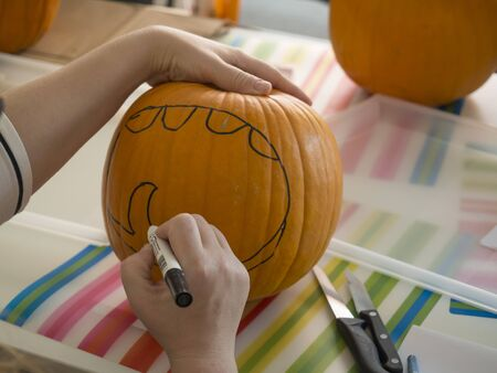 Process of carving pumpkin to make Jack-o-lantern. Creating traditional decoration for Halloween and Thanksgiving. Woman drawing decor on big orange pumpkin Imagens
