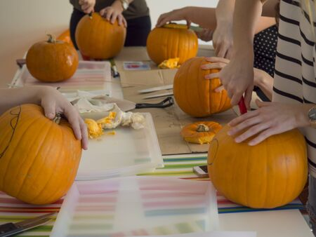 Group of people carving pumpkin to make Jack-o-lantern. Creating traditional decoration for Halloween and Thanksgiving. Cutted orange pumpkin lay on table.
