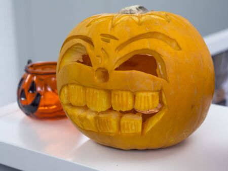 Halloween big orange pumpkin decorated with scary face. Jack O Lantern on white table background Imagens