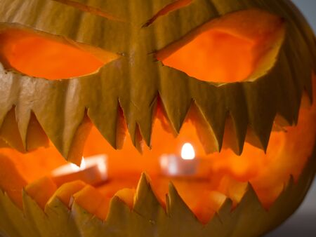 Close up Halloween big orange pumpkin decorated with scary face and tea light. Jack O Lantern decoration. Imagens