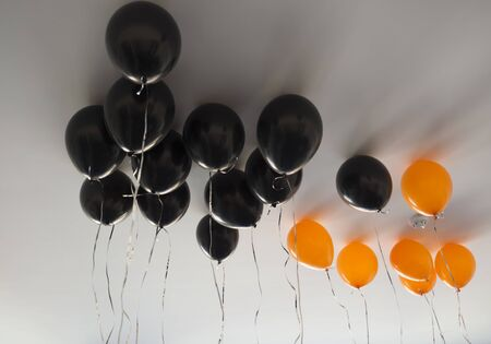 bunch of orange and black air balloons for halloween or birthday over white ceiling background. Holidays, decoration and party concept
