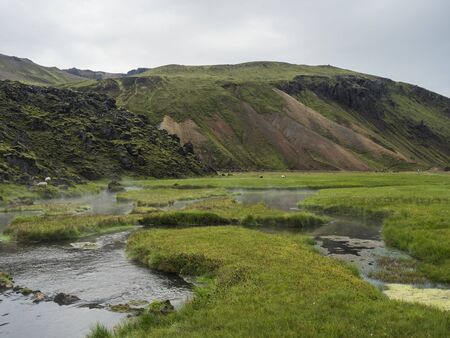 View on geothermal area with natural hot spring, thermal baths in Landmannalaugar camp site, Iceland. Grass meadow, lava fields and mountains in background. Imagens