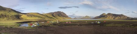 Panoramic landscape with colorful tents at camping site on blue Alftavatn lake with green hills and glacier in beautiful landscape of the Fjallabak Nature Reserve in the Highlands of Iceland, part of Laugavegur hiking trail