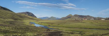Panoramic landscape with mountain huts at camping site on blue Alftavatn lake with river, green hills and glacier in beautiful landscape of the Fjallabak Nature Reserve in the Highlands of Iceland part of Laugavegur hiking trail Imagens